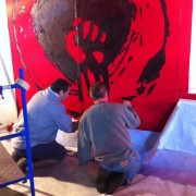 TRIO hand-painting the backdrop for Rise Against