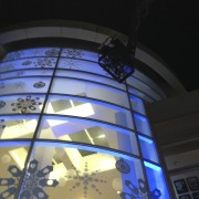 Installing adhesive snowflakes to the holiday window display at the Paley Media Center