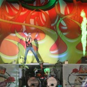 Poison on stage with TRIO hand-painted backdrop in Dallas